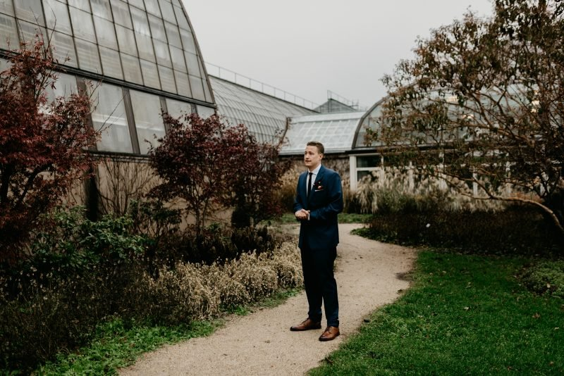 man in a suit waiting in a garden