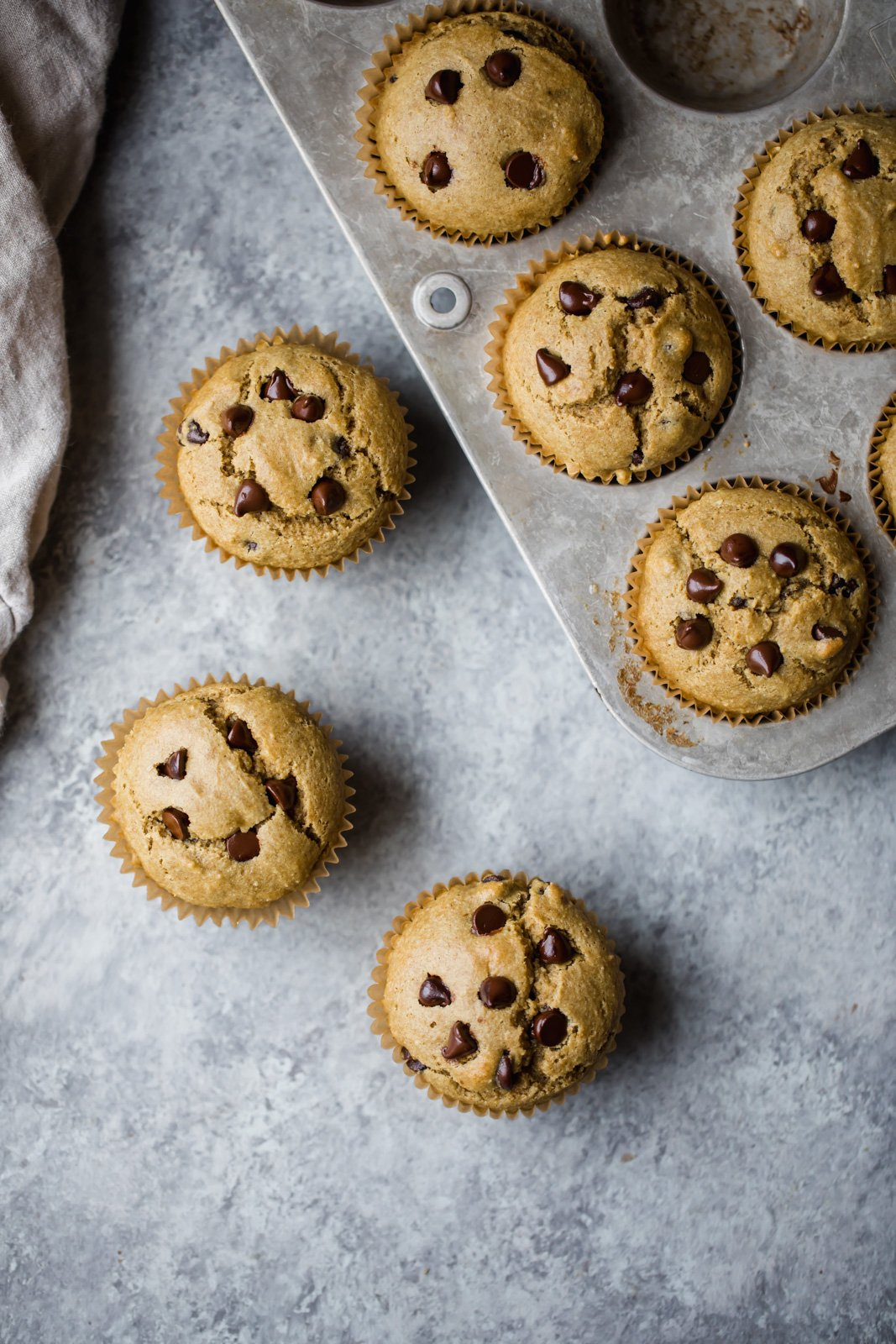gluten free chocolate chip muffins on a board and in a muffin tin