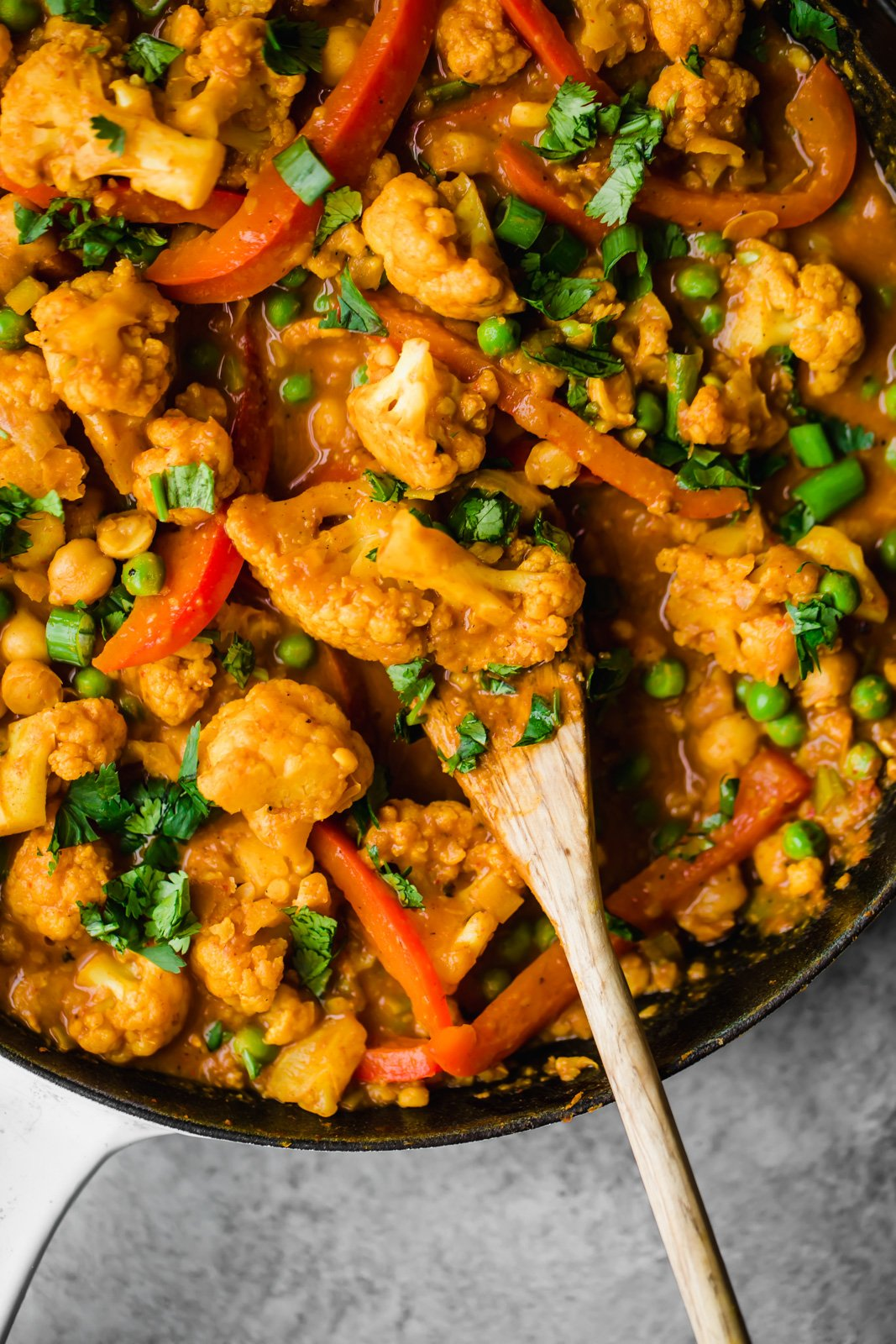 Pan of chickpea curry with cauliflower, red peppers, and peas