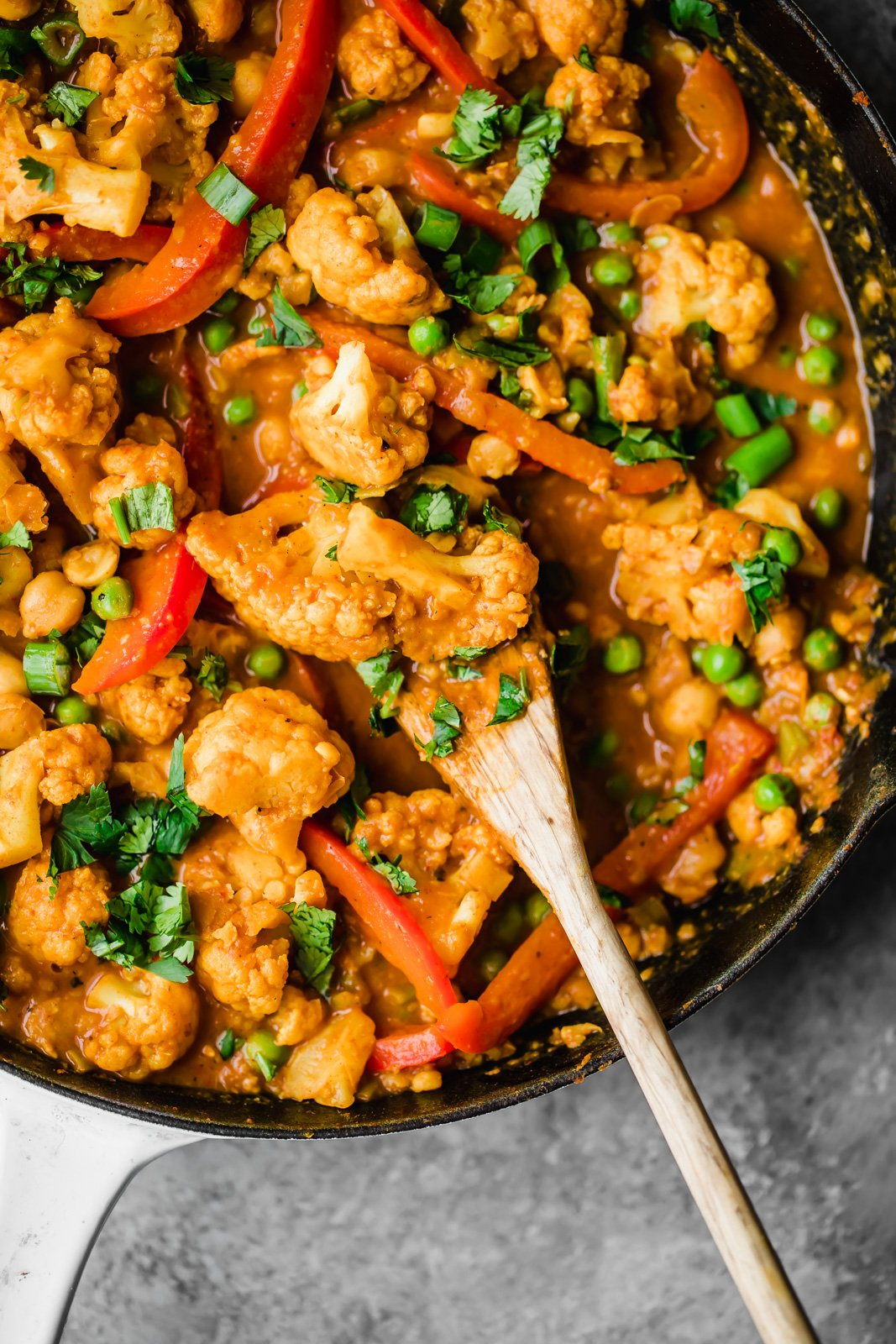 healthy 30-minute meals: cauliflower curry in a skillet with a wooden spoon