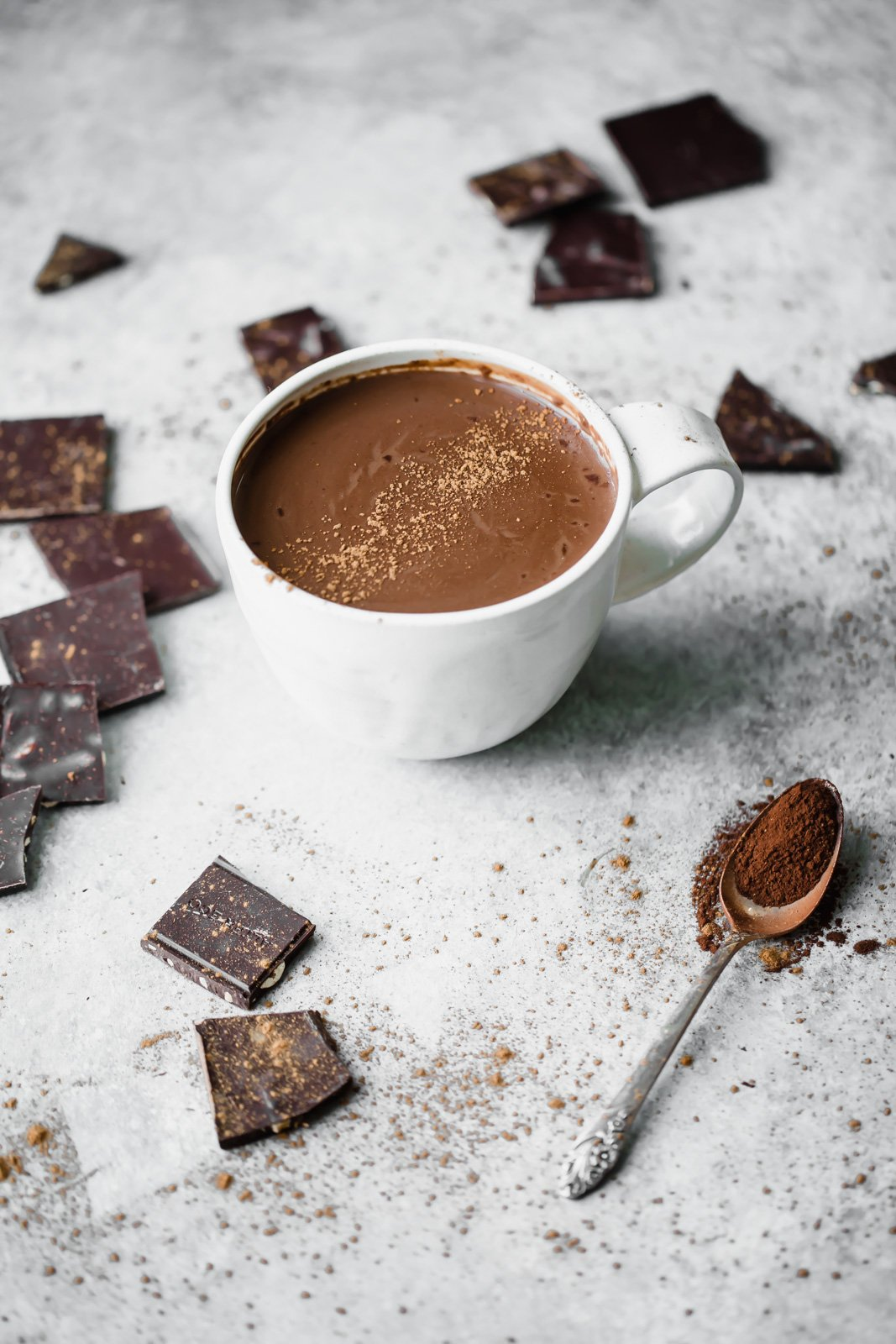 vegan hot chocolate in a mug next to squares of dark chocolate
