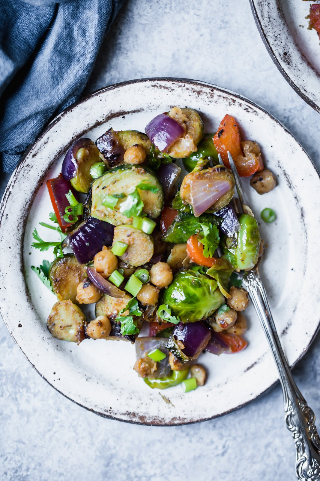 chickpeas, brussels sprouts and red onion on a white plate with a silver fork