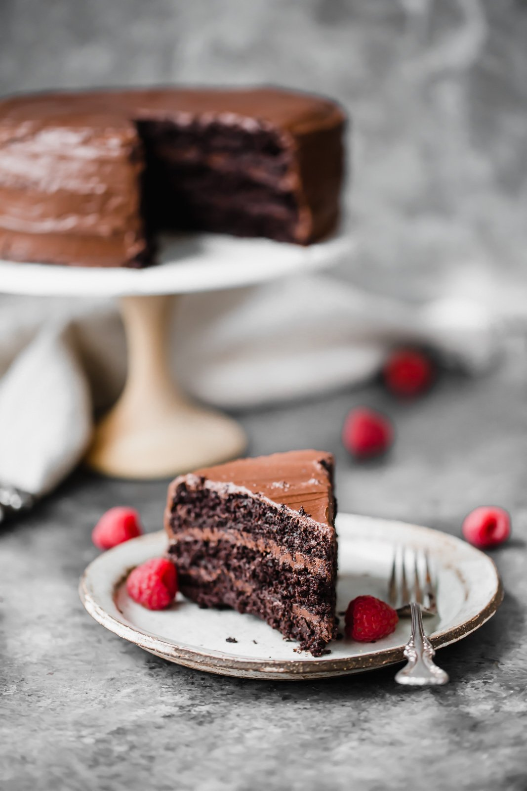 chocolate cake on a plate with raspberries