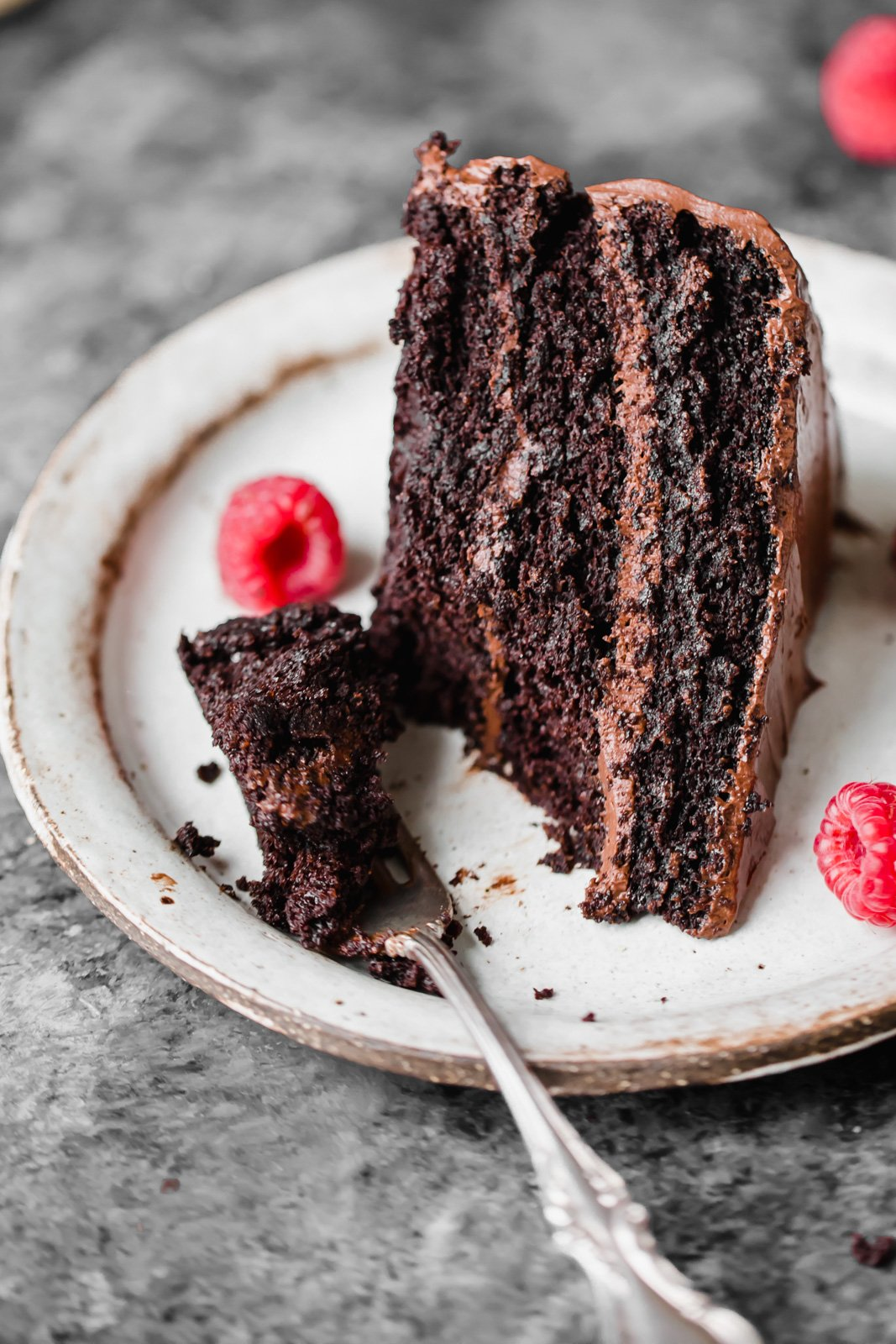 chocolate cake on a plate with raspberries and a fork