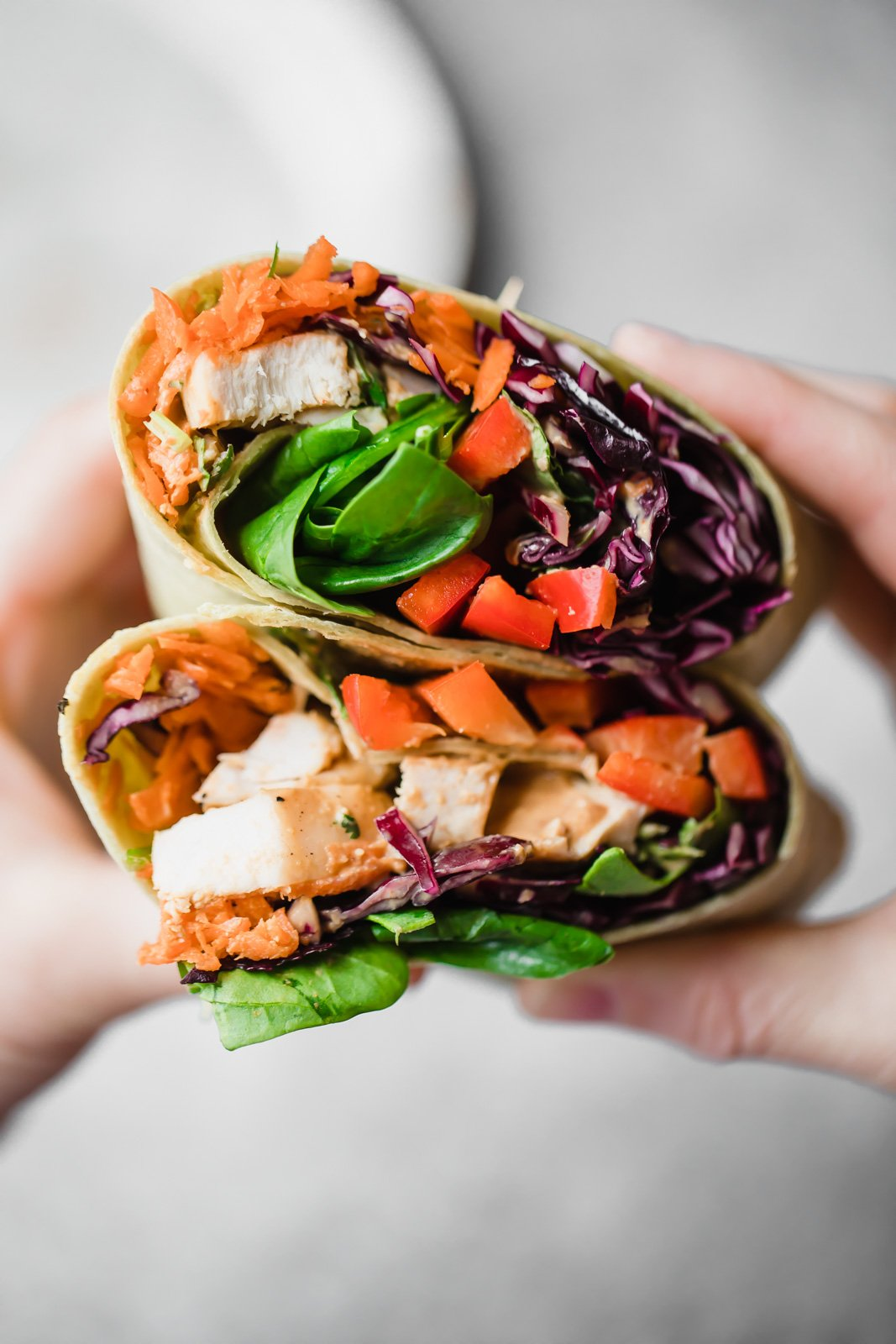 healthy 30-minute meals: hands holding a thai chicken wrap