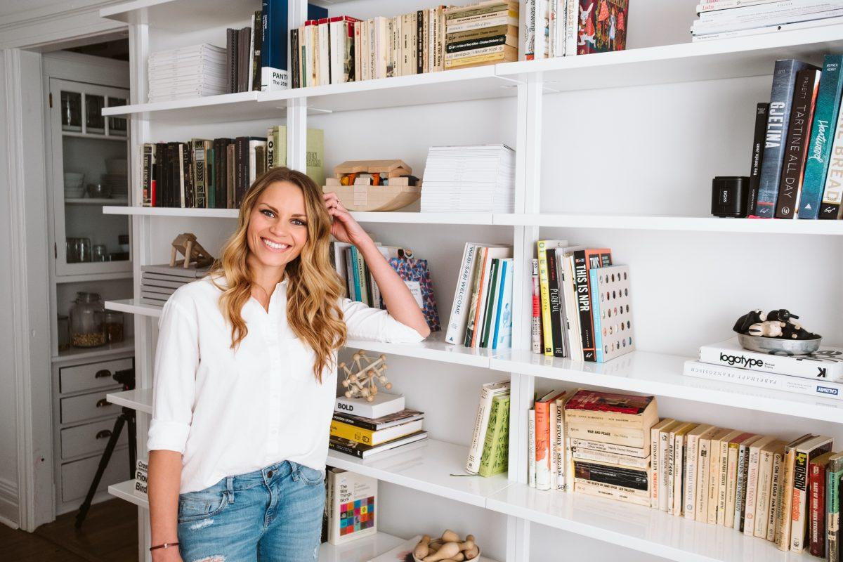 monique leaning against a bookshelf