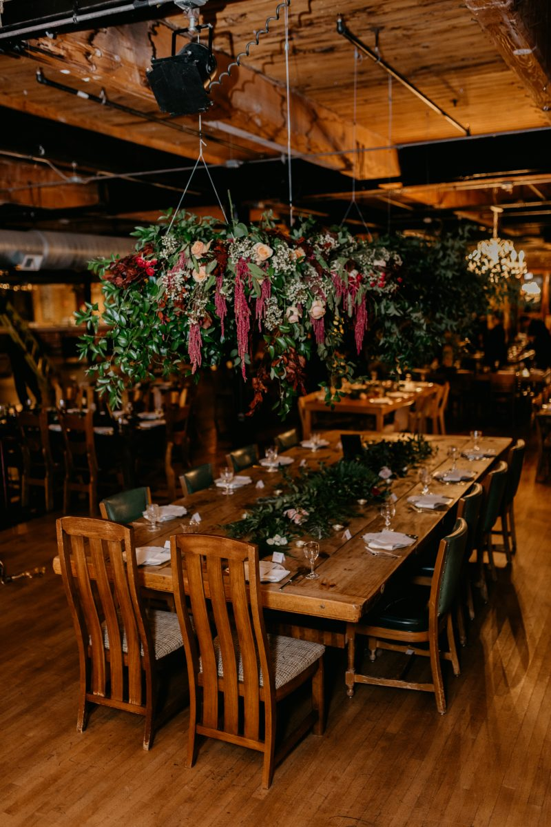 long table with a flower arrangement hanging over it