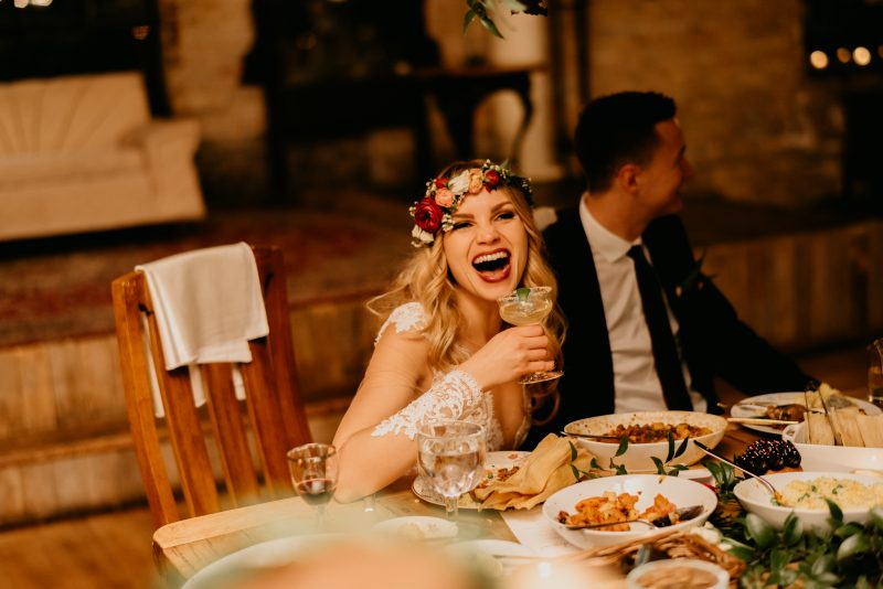bride laughing with a drink in her hand