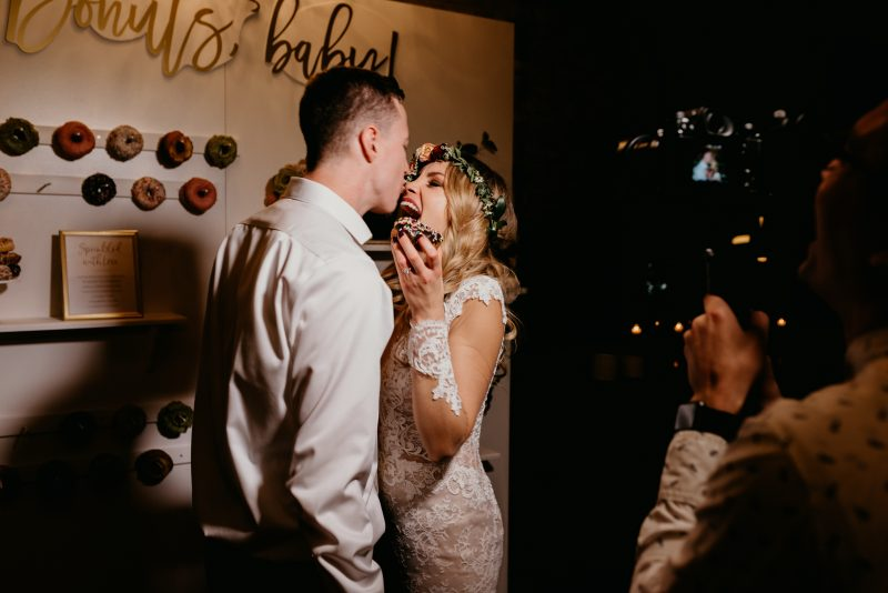 bride and groom kissing with a donut in hand
