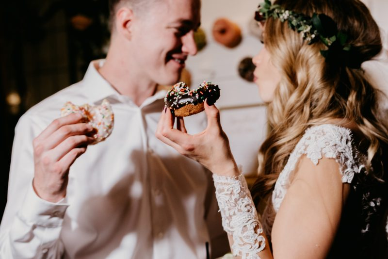 bride and groom holding donuts