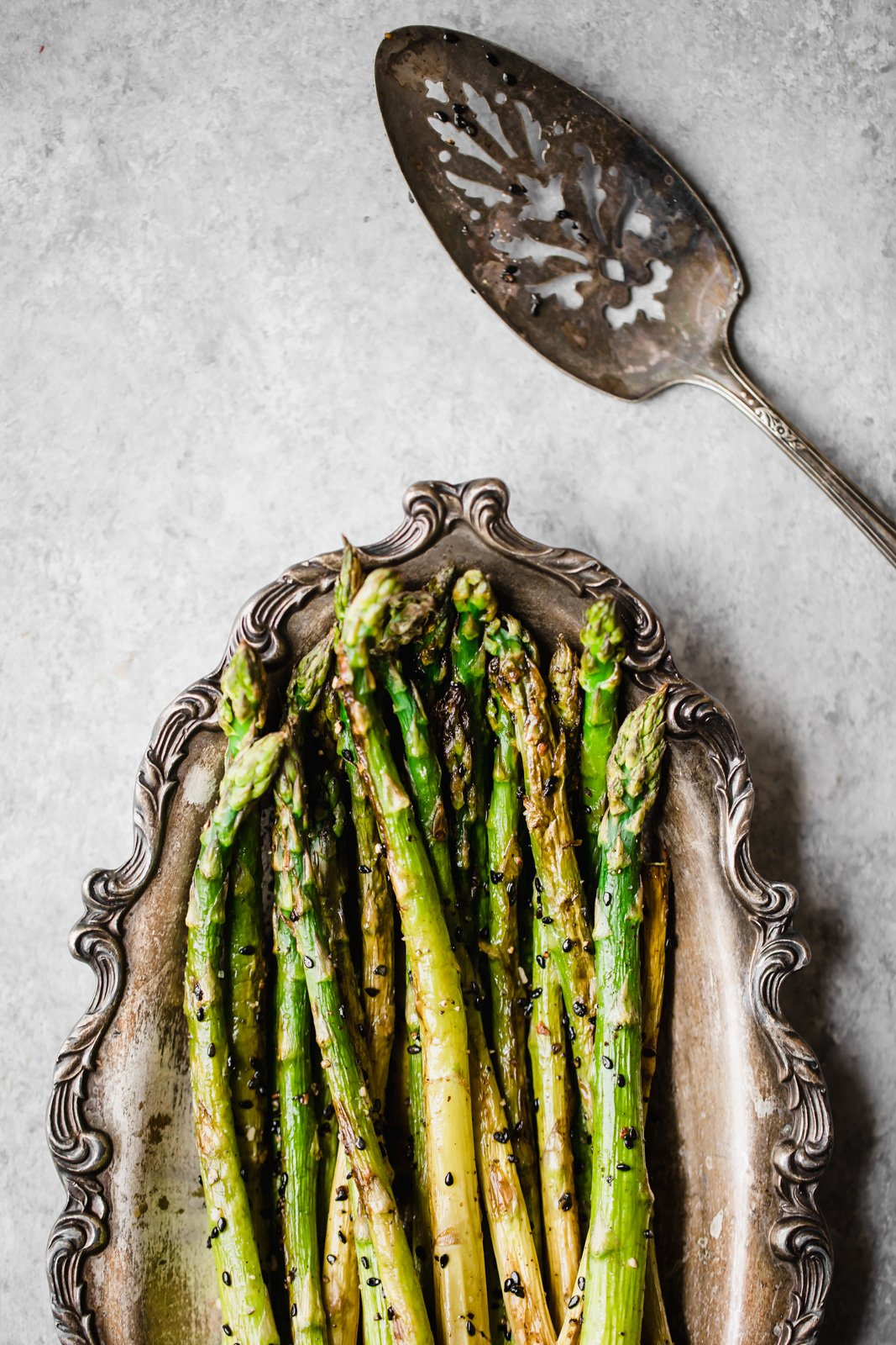 sesame garlic roasted asparagus on a platter with a serving spoon