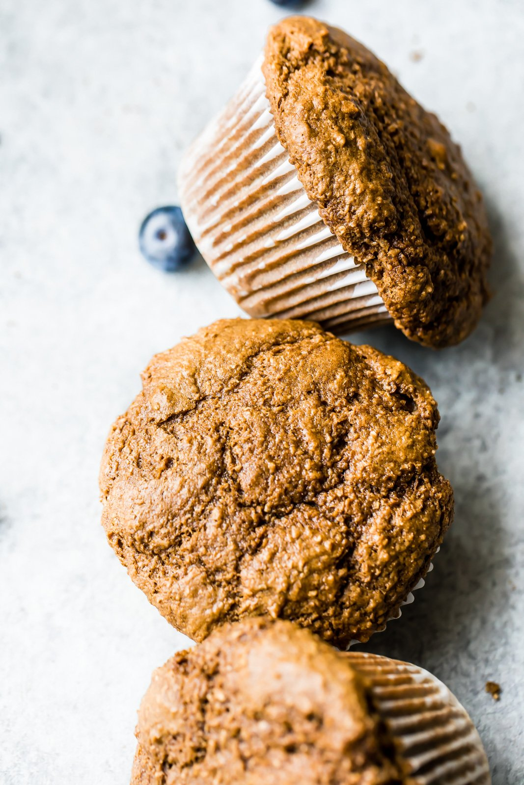 healthy bran muffins on a board with one blueberry