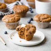 healthy bran muffin on a plate with healthy bran muffins in the background