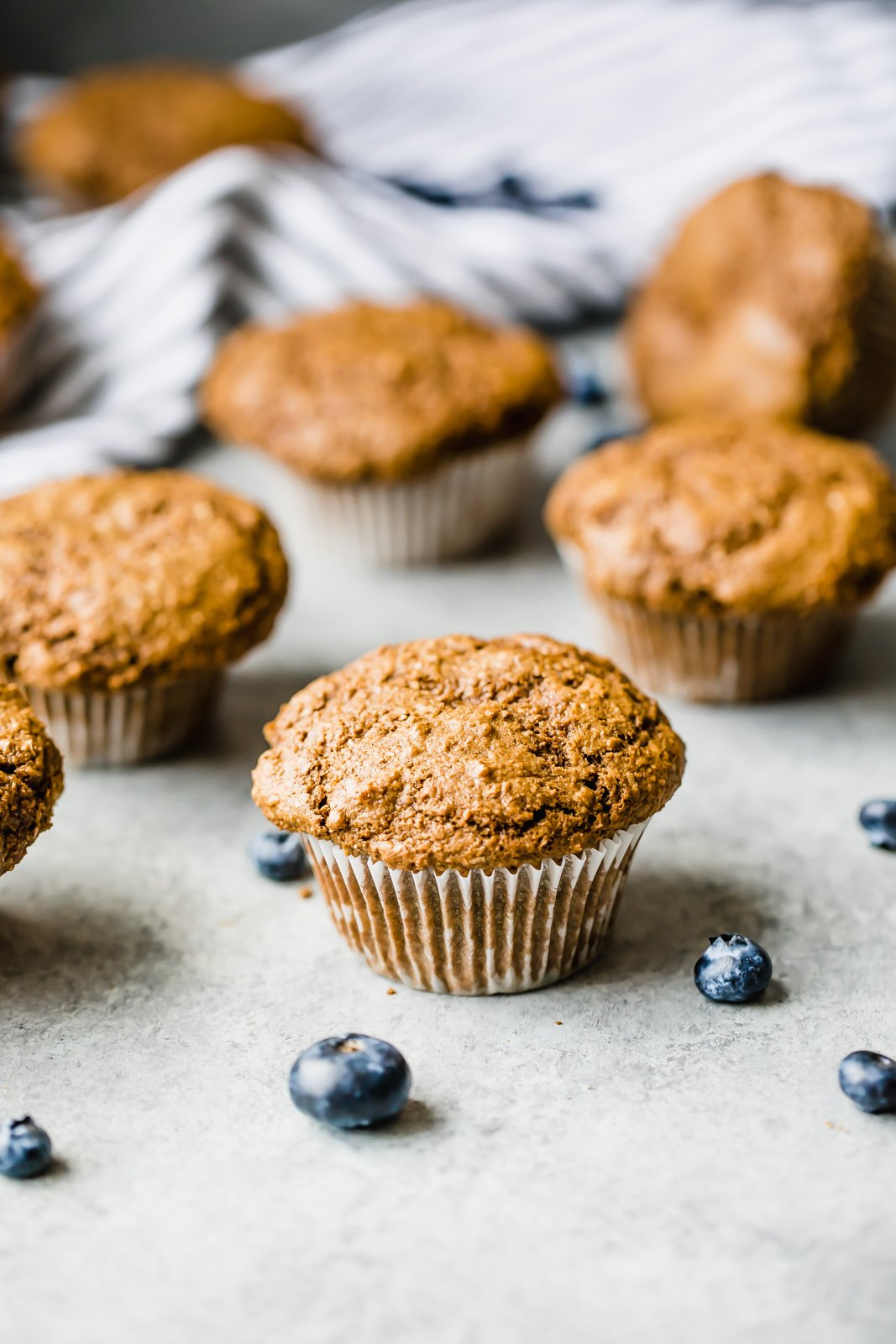 healthy bran muffin with blueberries on a grey board