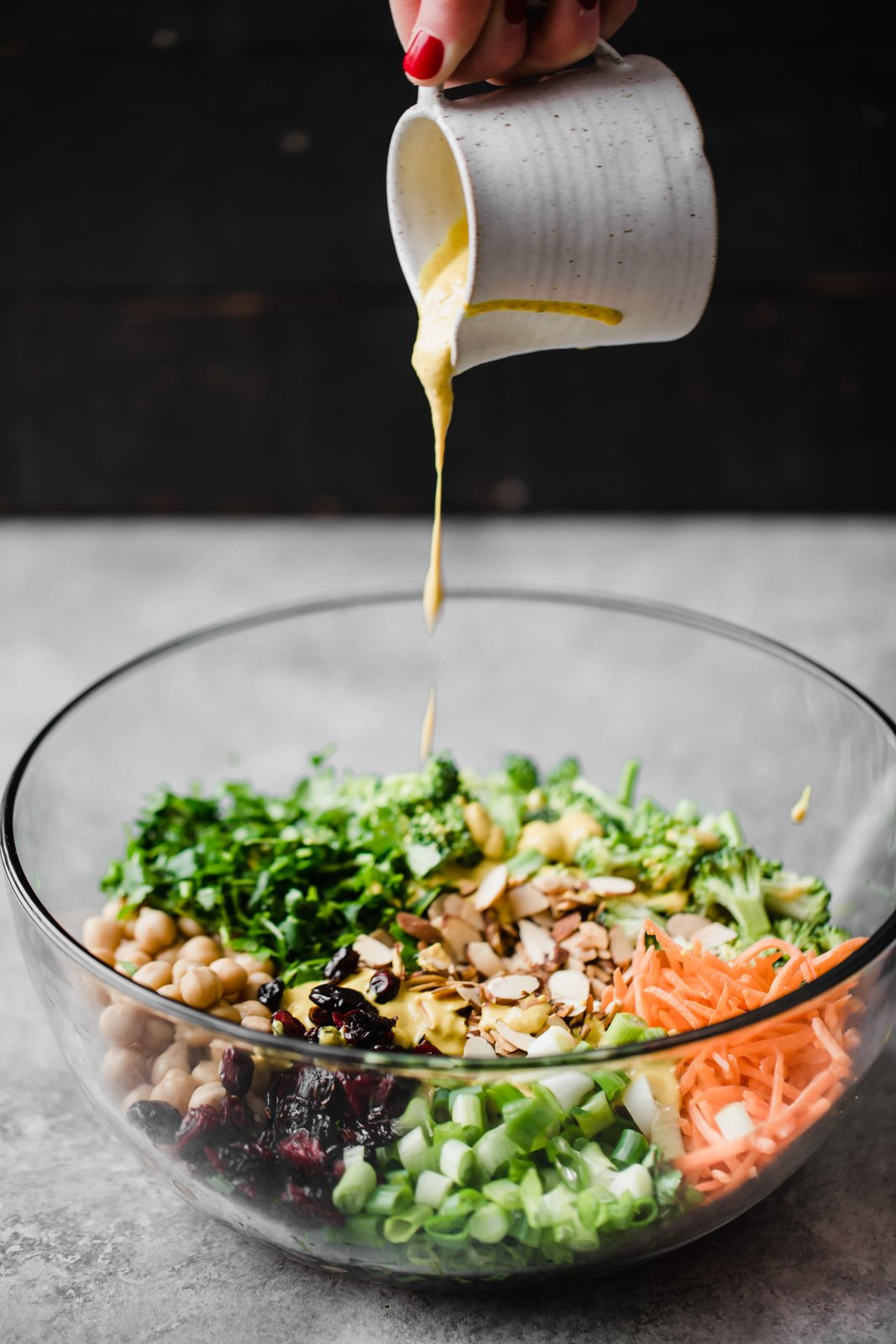 tahini dressing pouring into glass bowl with broccoli chickpea salad