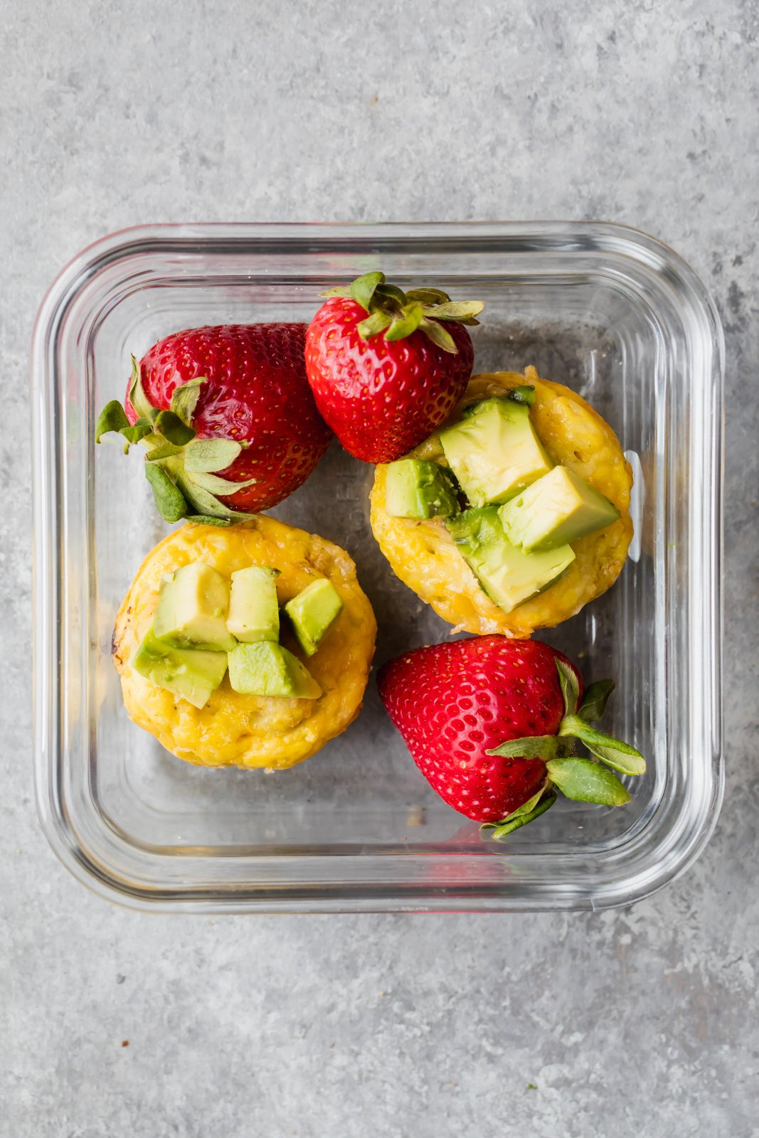 sausage, egg and cheese muffins topped with avocado in a glass container with strawberries