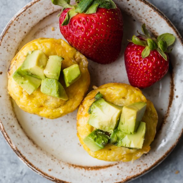 sausage egg and cheese muffins on a plate with strawberries