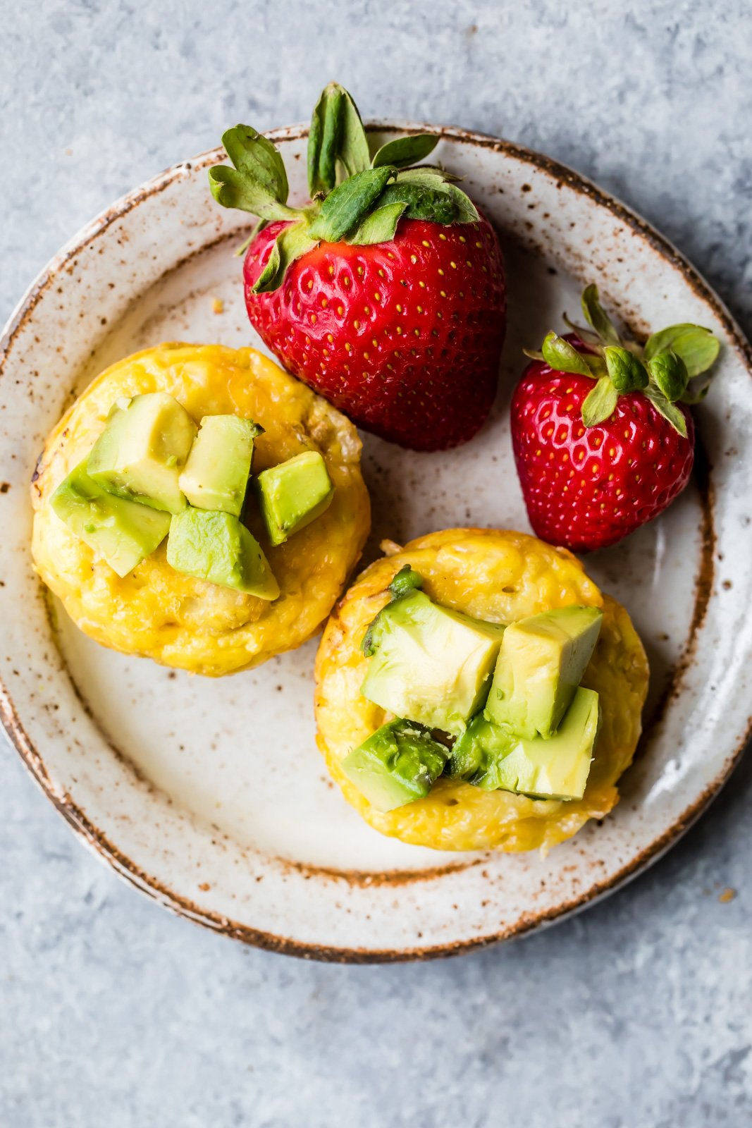 sausage, egg and cheese muffins topped with avocado on a plate with strawberries