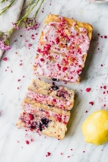 paleo lemon blueberry bread with pink glaze next to a lemon