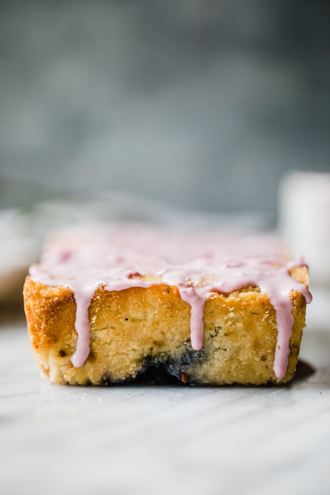 paleo lemon blueberry bread drizzled with pink glaze on a marble slab