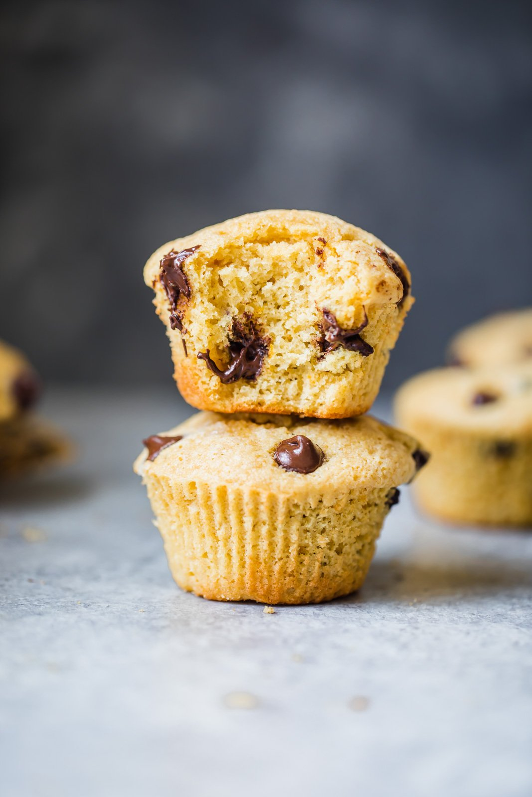 Two orange chocolate chip muffins stacked