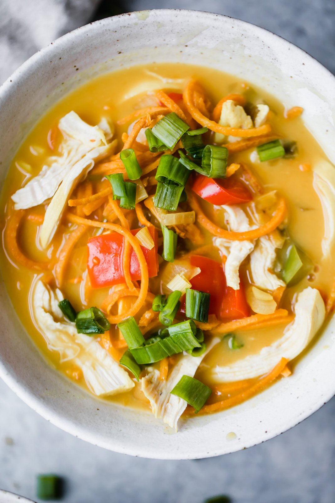 chicken sweet potato noodle soup in a bowl with green onion