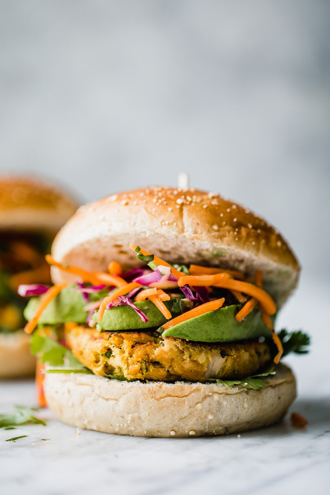 Tuna burger topped with avocado and cabbage slaw
