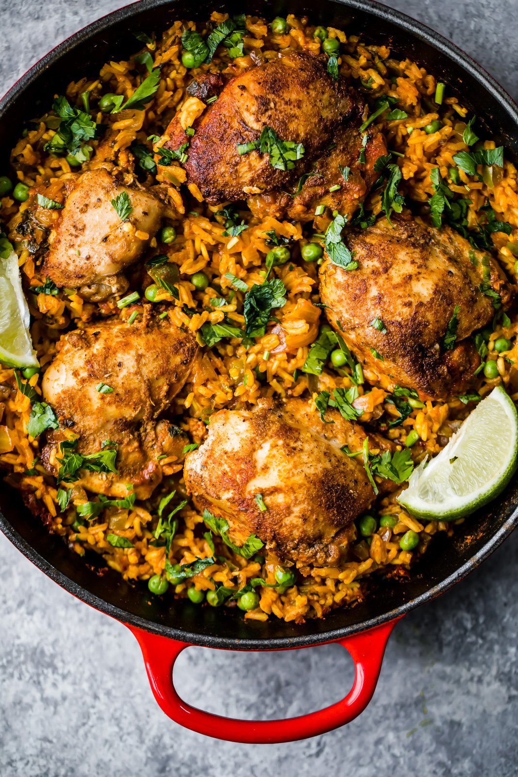 chicken and rice in a pan garnished with cilantro and lime
