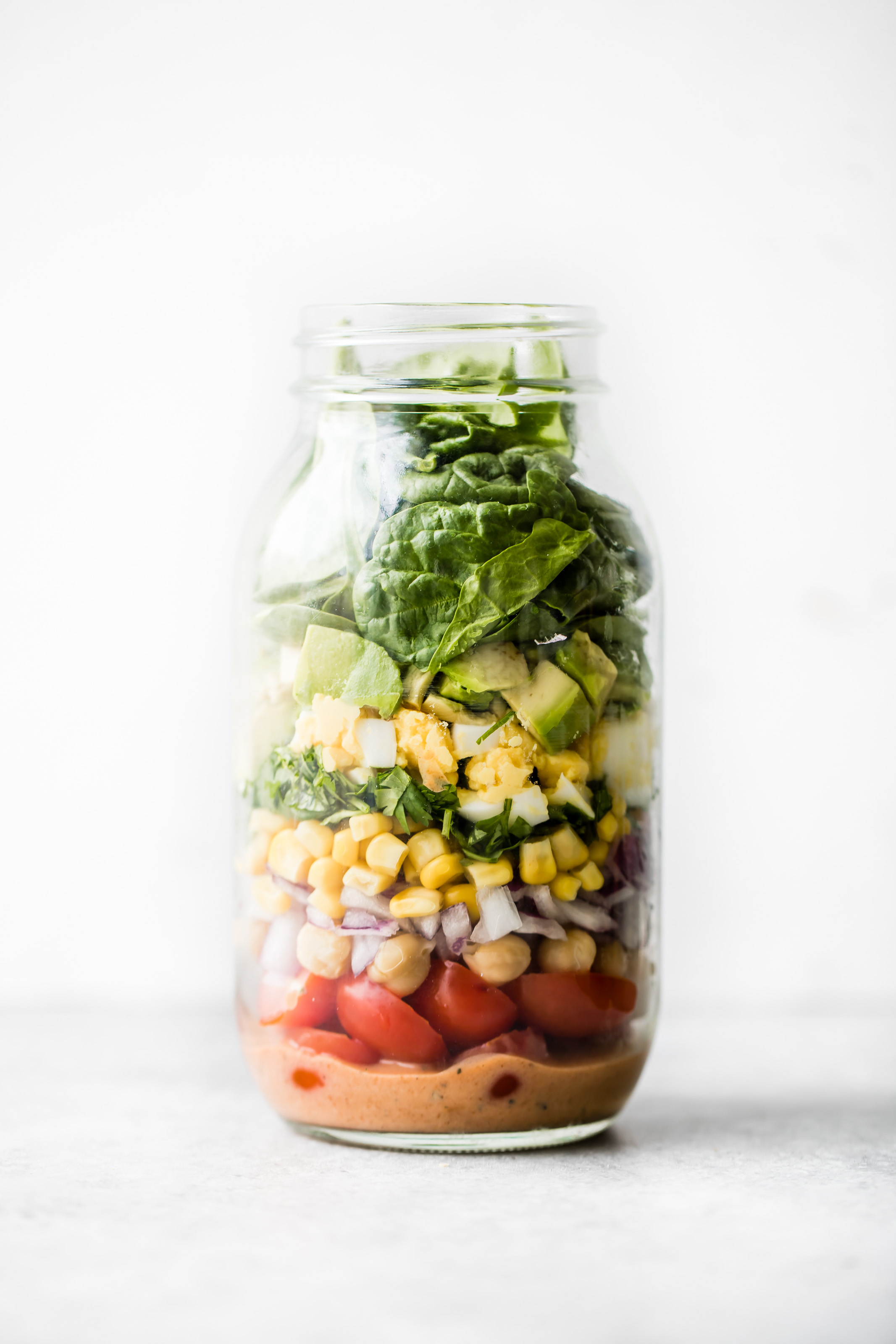 Delicious vegetarian BBQ Chickpea Cobb Salad with tomatoes, sweet corn, chickpeas, herbs and a kick of heat! Dressed with a healthier greek yogurt BBQ ranch dressing. Easy to make and great for meal prep!