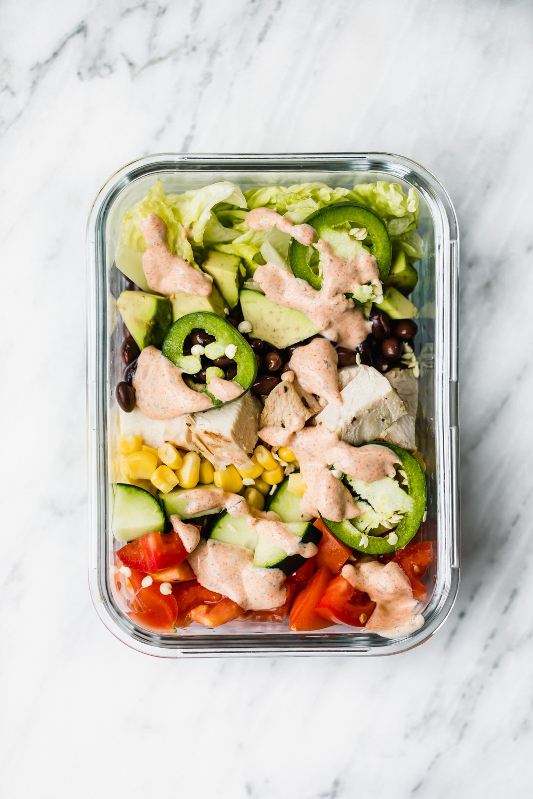 southwest chicken salad drizzled with dressing in a rectangle glass container