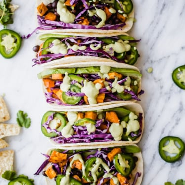 sweet potato black bean tacos lined up on a marble board