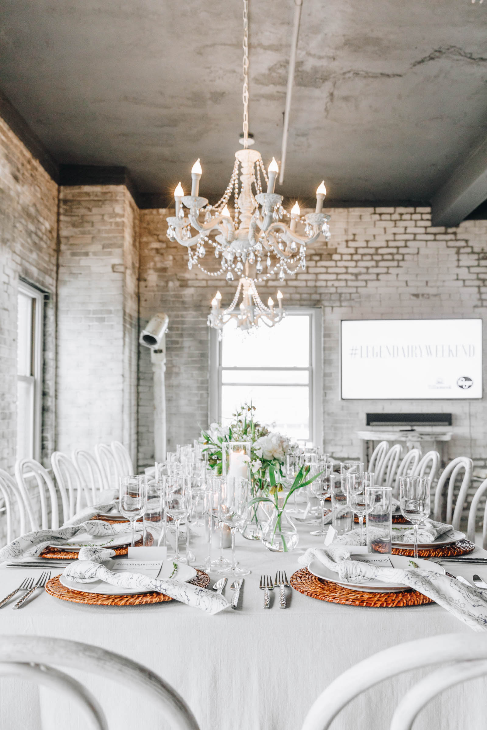 white table setting with a white hanging chandelier