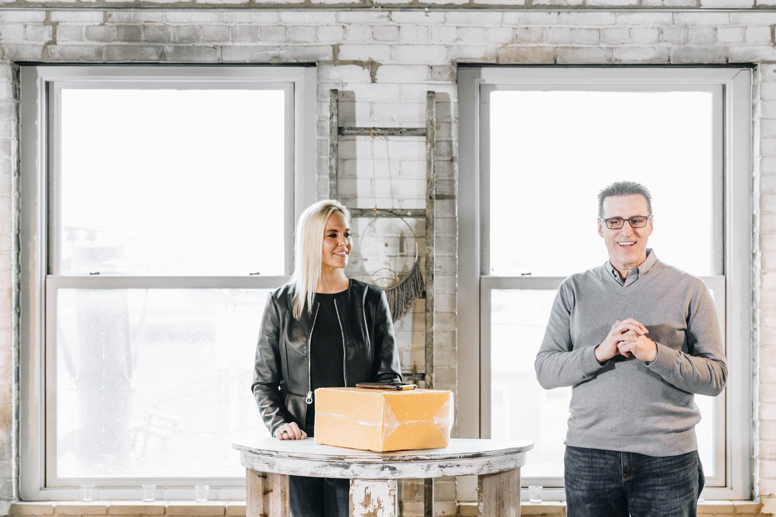 two people standing next to a cheese block