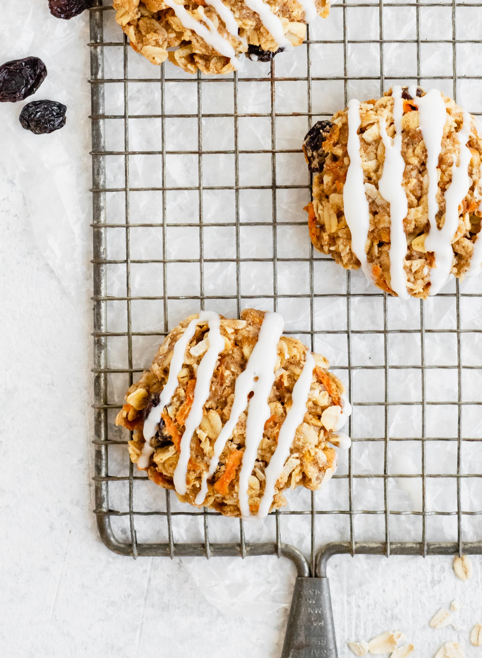 Three carrot cake cookies on a wire rack with raisins