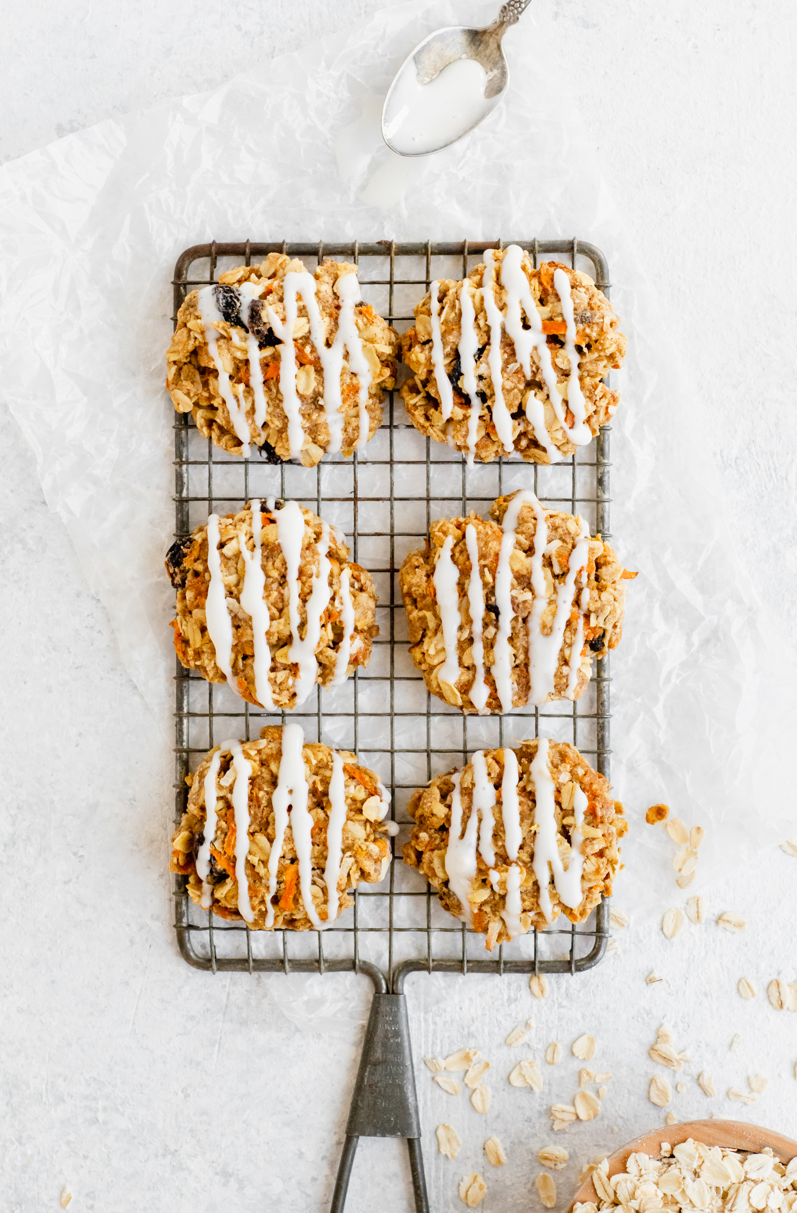 Six carrot cake cookies lined up on a wire rack with a spoon and oats next to it