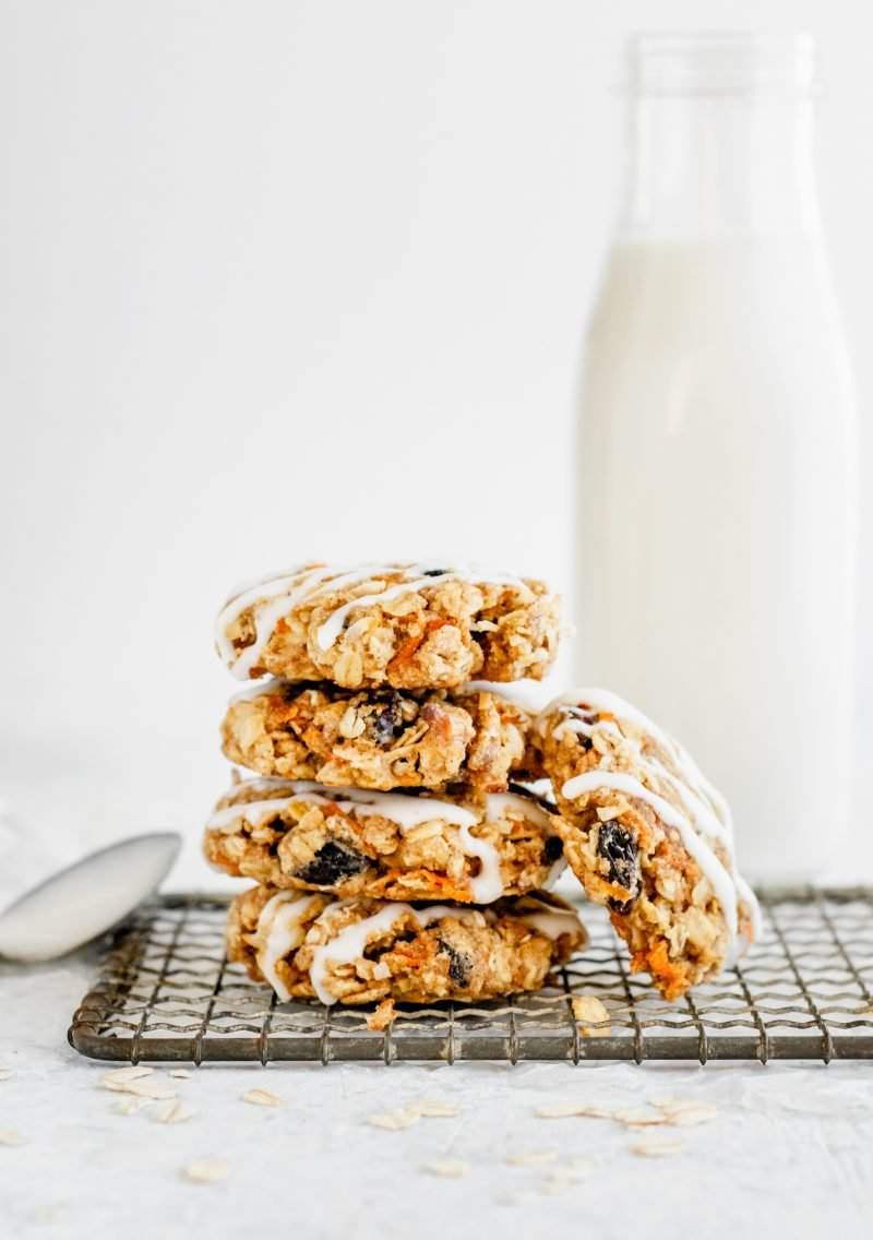 healthy carrot cake cookies stacked on top of each other with a milk bottle in the background