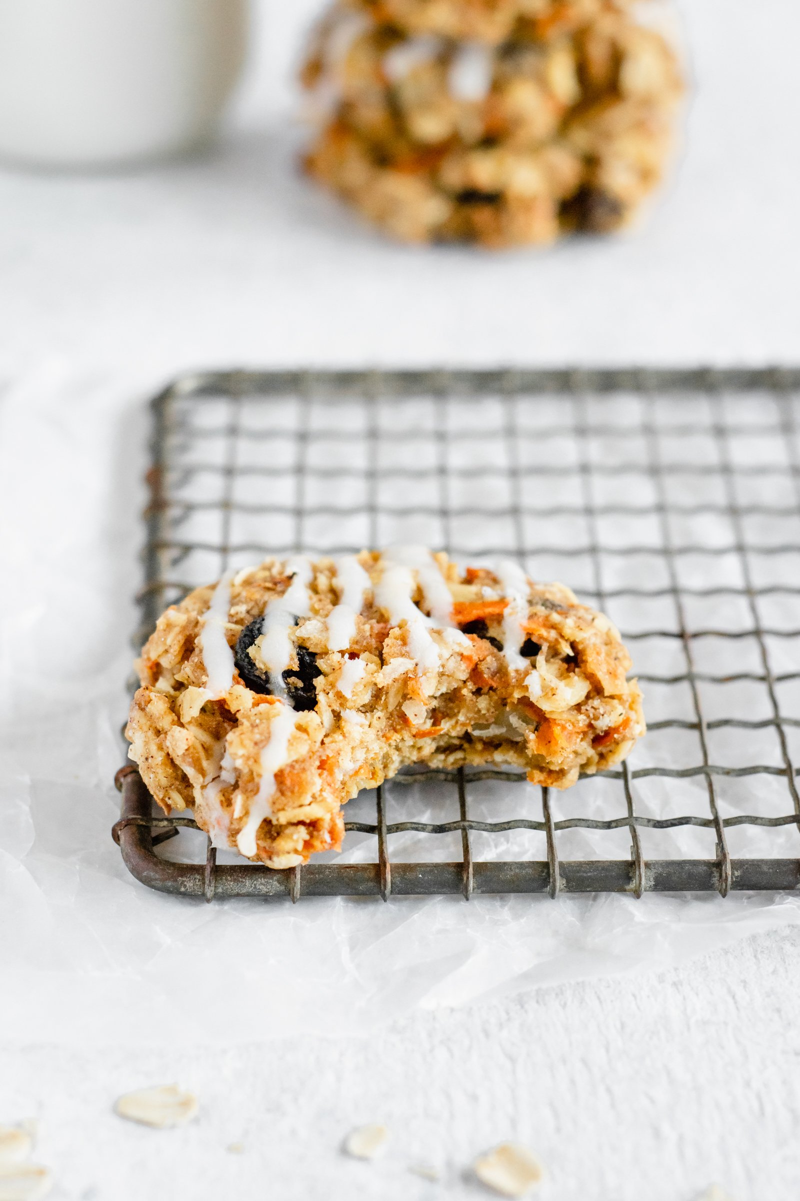Carrot cake cookie with a bite taken out on top of a wire rack