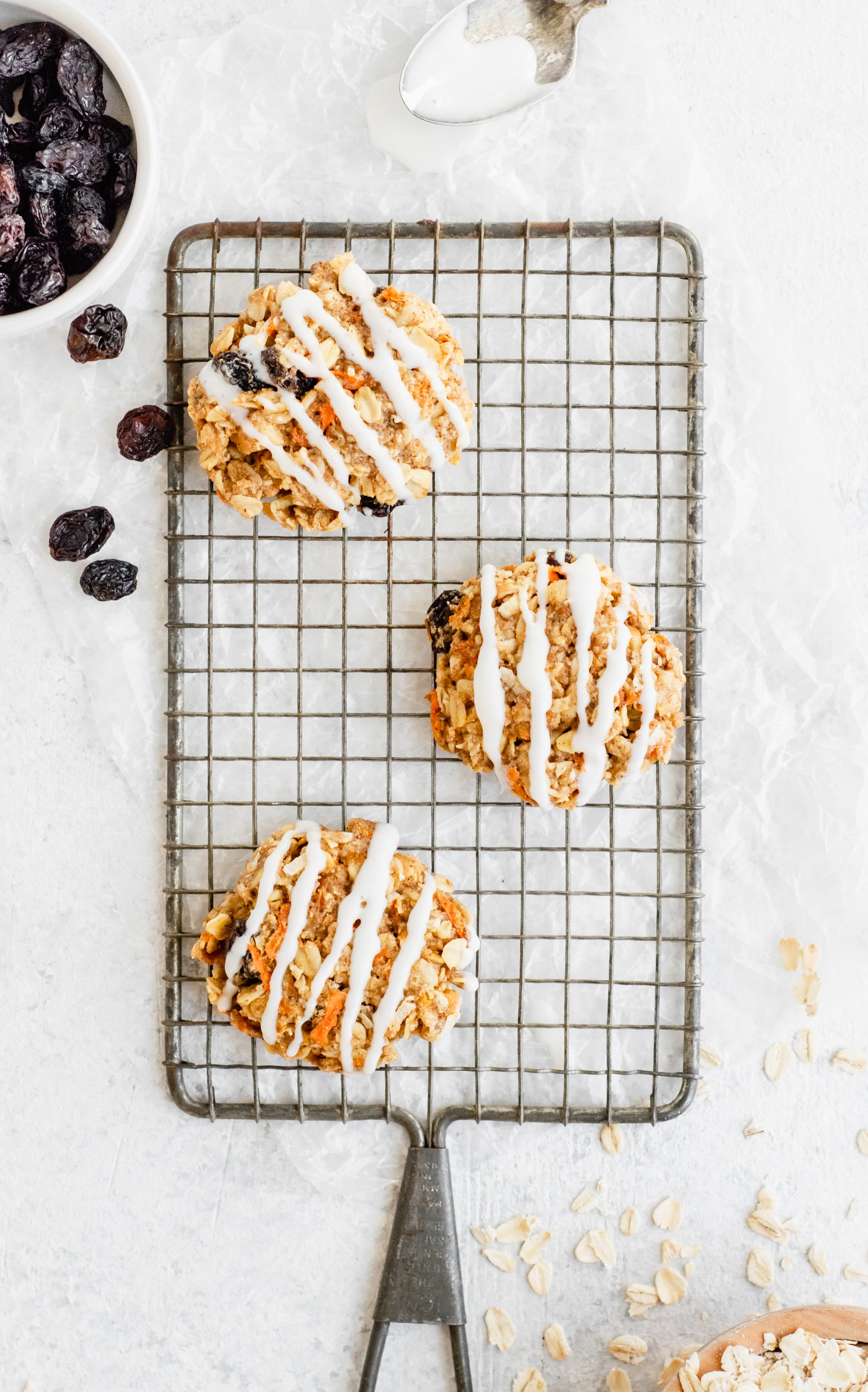 Three carrot cake oatmeal cookies on a wire rack with raisins and oats on the side