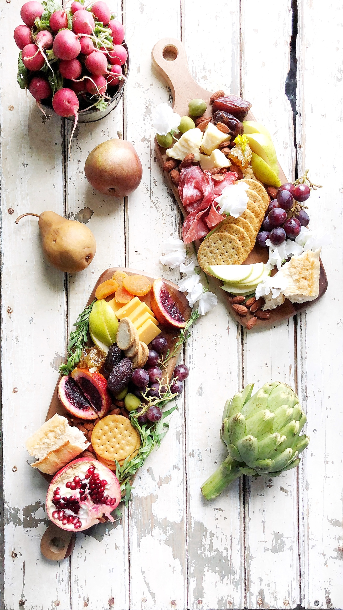 two charcuterie boards next to an artichoke, radishes and pears