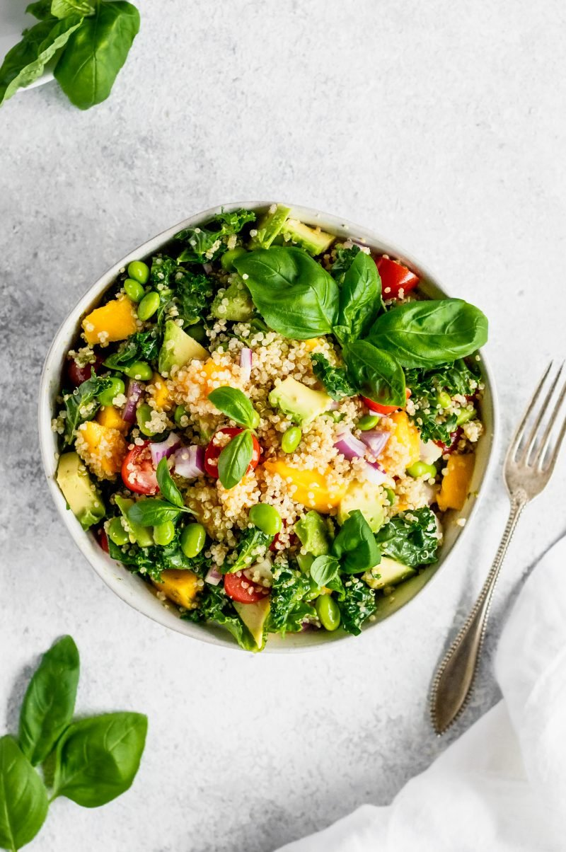 Kale quinoa salad with mango and edamame in a bowl next to a fork