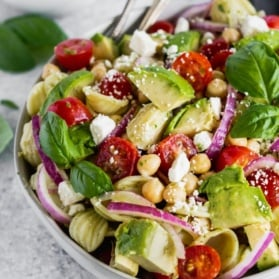 healthy pasta salad recipe in a bowl with avocado, tomatoes, and feta