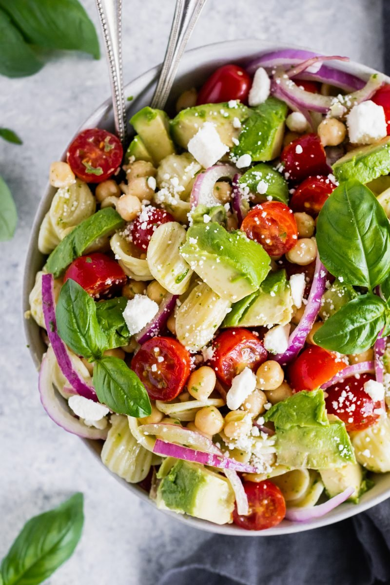 chickpea pasta salad in a bowl with avocado, tomato, red onion and feta