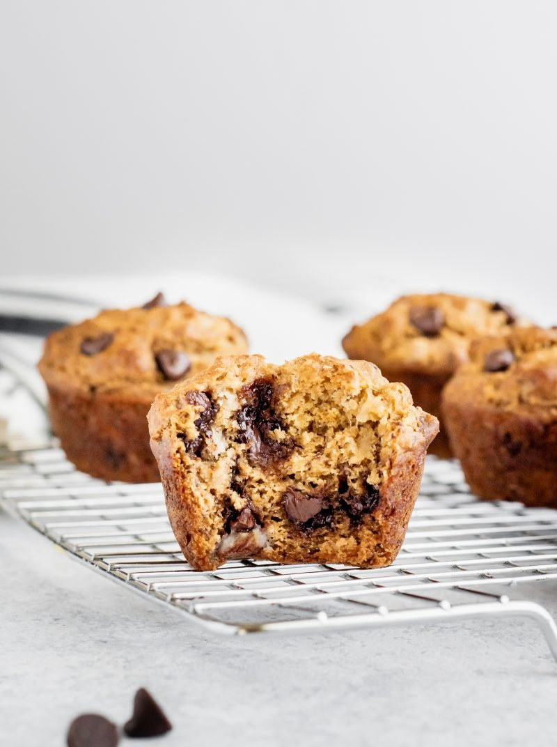 skinny banana chocolate chip muffin with a bite taken out on a wire rack