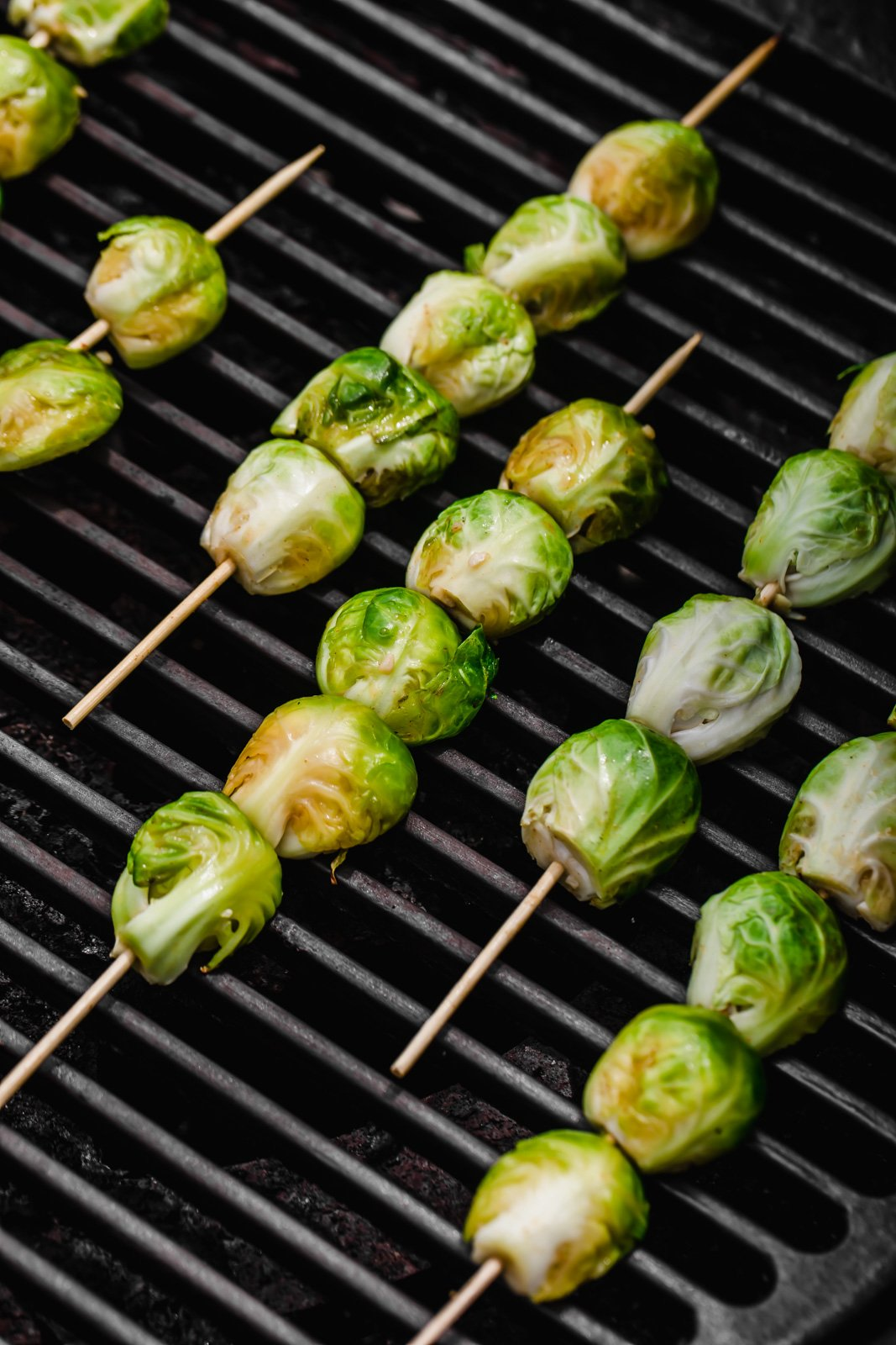 Spicy maple grilled brussels sprouts on skewers on top of a grill
