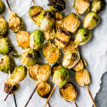 Spicy maple grilled brussels sprouts on skewers on top of parchment paper