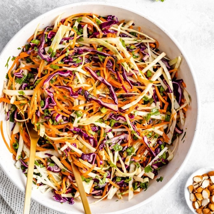 healthy coleslaw in a bowl with two serving spoons