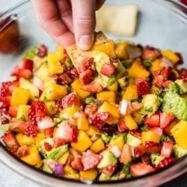 dipping a chip into Avocado Strawberry Mango Salsa