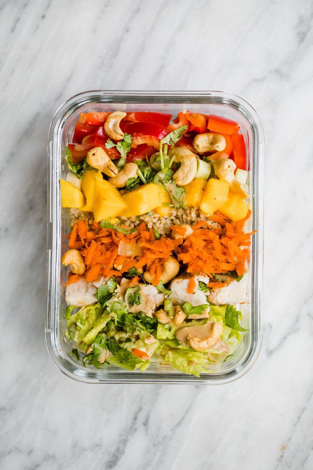 Romaine, cashews, chicken, shredded carrots, mango and red bell pepper in a glass container on a marble board