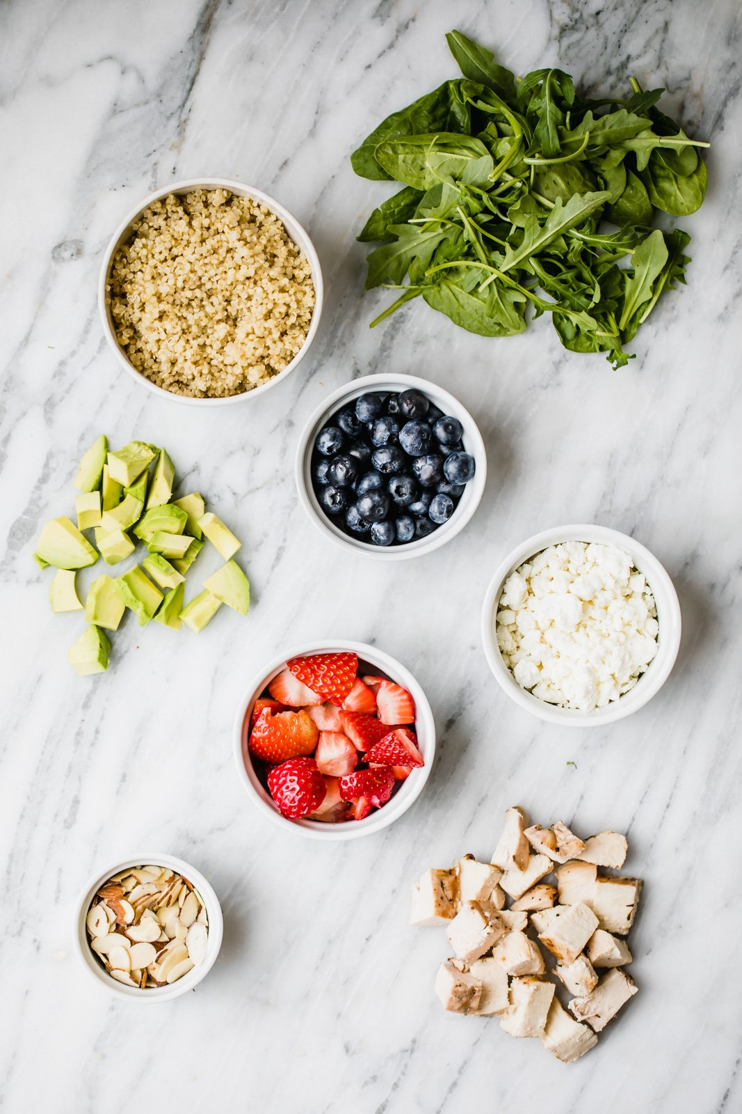 ingredients for chicken berry quinoa salad on a marble slab
