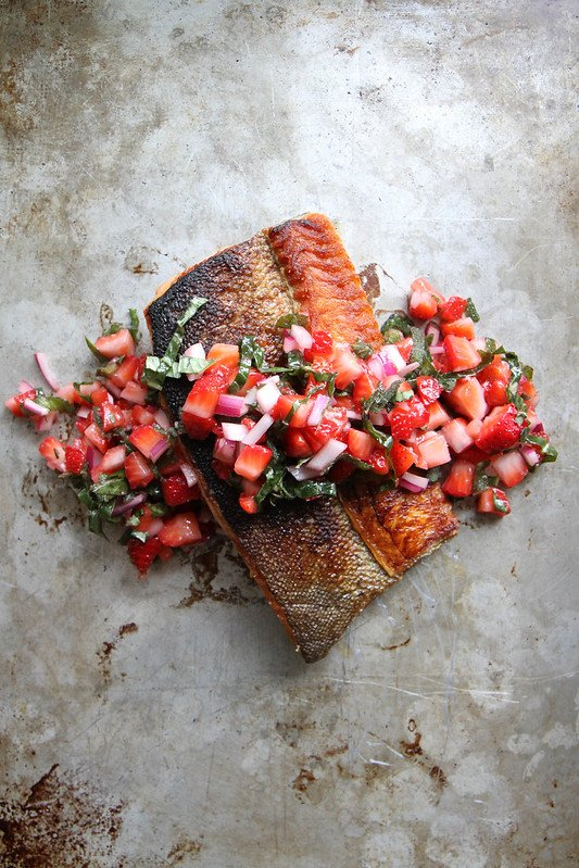 salmon topped with strawberry salsa on a baking sheet